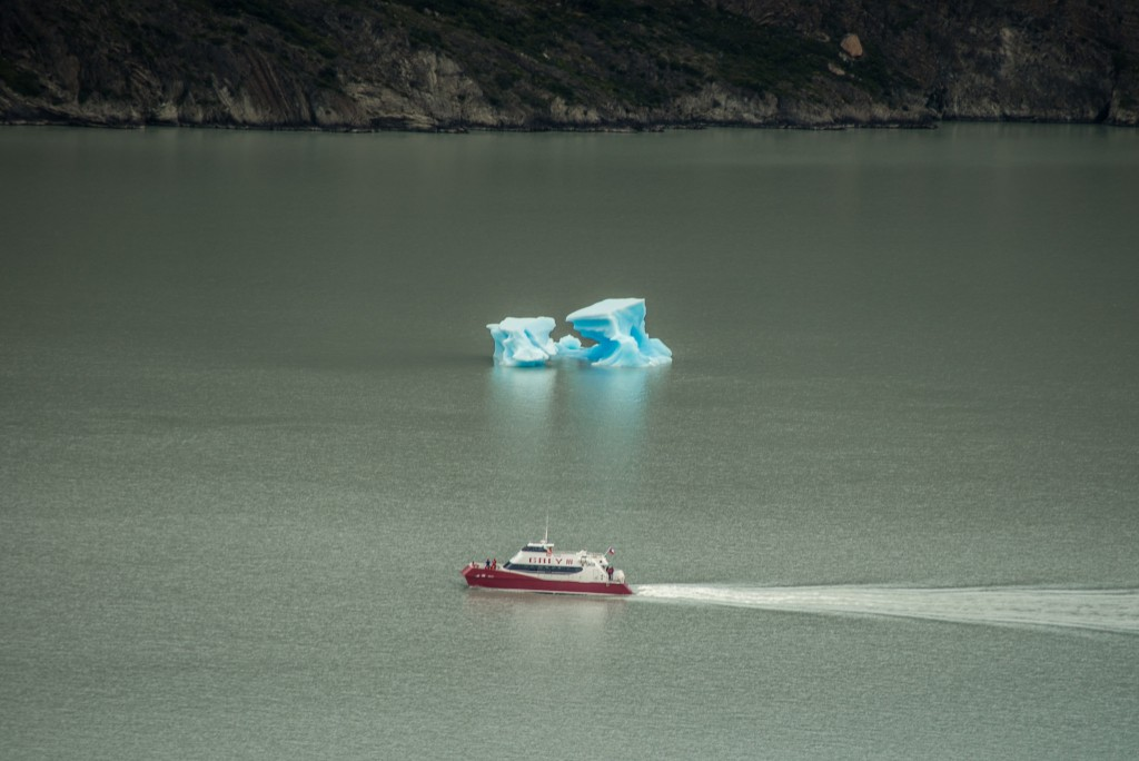 A boat of giggly backpackers goes up close to the calving Glacier Grey